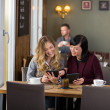 Stock Photo: Female Friends Using Digital Tablets At Table