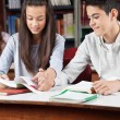 Teenage Couple Reading Book Together In Library — Stock Photo #33252815