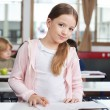 Little Girl Studying While Standing At Desk — Stock Photo