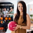 Happy Woman Holding Bowling Ball in Club — Stock Photo #33253901