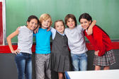 Happy Schoolchildren With Arms Around Standing Together In Class — Stock Photo