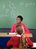 Schoolgirl Sitting At Desk With Teacher In Background — Stock Photo