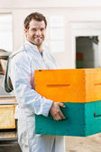 Happy Male Beekeeper Carrying Stack Of Honeycomb Crates — Stock Photo