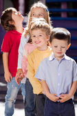 Boy Standing With Friends In A Row At Kindergarten — Stock Photo