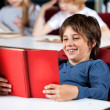 Schoolboy Smiling While Reading Book At Table In Library — Stok fotoğraf #33451207