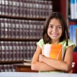 Cute Schoolgirl Holding Book While Sitting In Library — Stock Photo #33451951