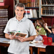 Confident Male Librarian Holding Books While Standing In Library — Stock Photo #33452357