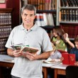 Confident Male Librarian Holding Books While Standing In Library — Stock Photo