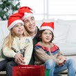 Father And Siblings Wearing Santa Hats During Christmas — Stock Photo #33452725