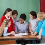 Female Professor Teaching Students At Desk — Stock Photo