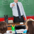 Angry Teacher Pointing At Schoolboy In Classroom — Stock Photo #33454103