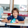 Schoolboy Sitting With Books And Globe At Desk — Stock Photo #33456963