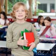 Schoolboy Holding Books With Classmates In Background — Stock Photo #33457697