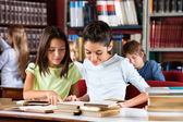 Schoolgirls Reading Book Together At Table In Library — Stock Photo