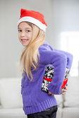 Smiling Girl Hiding Christmas Present Behind Back — Stock Photo