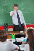 Angry Teacher Pointing At Schoolboy In Classroom — Stock Photo