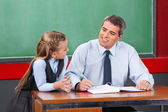 Male Teacher Looking At Schoolgirl In Classroom — Stock Photo