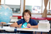 Schoolboy Sitting With Books And Globe At Desk — Stock Photo