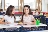 Schoolgirl Sitting With Classmate Looking At Her — Stock Photo