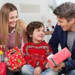 Parents With Christmas Presents Looking At Son — Stock Photo