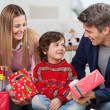 Parents With Christmas Presents Looking At Son — Stock Photo #33527637