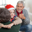 Son In Santa Hat Embracing Father — Stock Photo #33528777