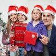 Family In Santa Hats With Christmas Present — Stock Photo