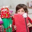 Boy Holding Christmas Gift In Front Of Face — Stock Photo