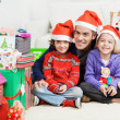 Father And Siblings Sitting By Stacked Christmas Presents — Stock Photo