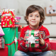 Smiling Boy Holding Christmas Gift At Home — Stock Photo #33531385