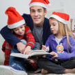 Father With Children Reading Book During Christmas — Stock Photo