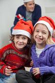 Happy Siblings Wearing Santa Hats At Home — Stock Photo