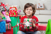 Smiling Boy Holding Christmas Gift At Home — Stock Photo