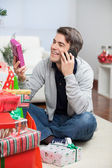 Man Holding Christmas Gift While Answering Mobilephone — Stock Photo