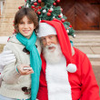 Santa Claus Embracing Boy With Smartphone Outside House — Stockfoto