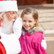 Santa Claus Whispering In Girl's Ear — Stock Photo
