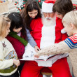Santa Claus With Children Pointing At Book — Stock Photo