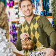 Man Holding Christmas Present And Bauble Basket In Store — Stock Photo #33729169