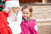 Santa Claus Whispering In Girl's Ear — Stock Photo