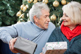 Senior Couple With Presents In Christmas Store — Stock Photo