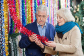 Couple Choosing Tinsels At Store — Stock Photo
