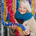 Woman Choosing Tinsels At Christmas Store — Stock Photo #33731785