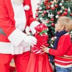 Santa Claus Giving Present To Boy — Stock Photo #33730015