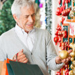 Man Choosing Christmas Ornaments — Stock Photo