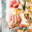 Man Holding Golden Christmas Bauble At Store — Stock Photo