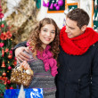 Couple With Bauble Basket In Store — Stockfoto