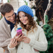 Couple With Christmas Present At Store — Stock Photo
