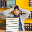Confused Man Looking At Stacked Books In Library — Stock Photo