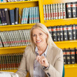 Confident Teacher With Books Sitting At Table In Library — Stock Photo