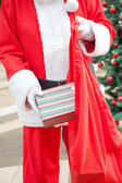 Santa Claus Putting Present In Bag Outdoors — Stock Photo